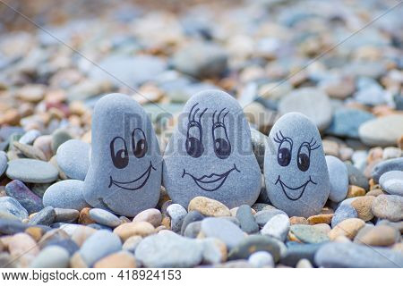 Pebbles With Drawn Faces In The Sand. Father, Mother And Daughter. Family Vocation Concept
