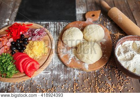 Pizza Dough With Ingredients On Wood Table