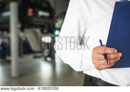 Master Receptionist In A Car Service Station With A Tablet For Recording Repairs And Maintenance. Re