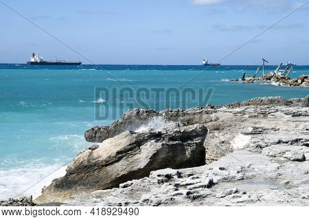 The Eroded Grand Bahama Island Coastline With A House Ruins And Industrial Ships In A Background.