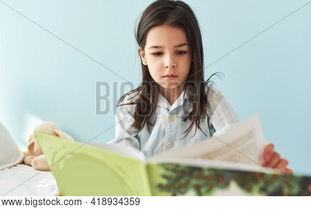 Candid Portrait Of A Cute Little Girl Sitting In The Bed And Reading The Fairy Tale Book. Kid In Paj