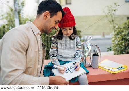 Horizontal Image Of Pretty Little Girl In Red Cap Drawing With Her Dad Together Outdoors After Schoo