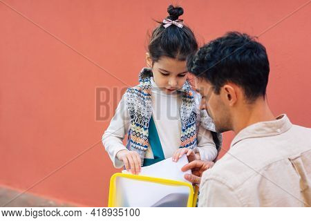 Rear View Of A Father Meeting His Little Girl After School. Father Enjoying The Time Together With H