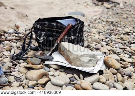 Geologists Bag With The Stones And Notes Papers And Hammer. Geology Science Concept. The Geologists