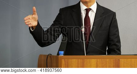A Man - A Lawyer, Politician, Businessman Or Official Speaks From The Rostrum. Gesture And Microphon