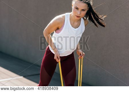 Sporty Young Woman Exercising With Resistance Band On A Sunny Day. Athlete Female Working Out With E