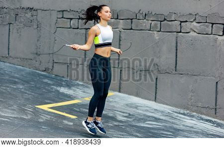 Full-length View Of Young Determined Woman Skipping With A Rope Outdoors Next To The Concrete Wall.