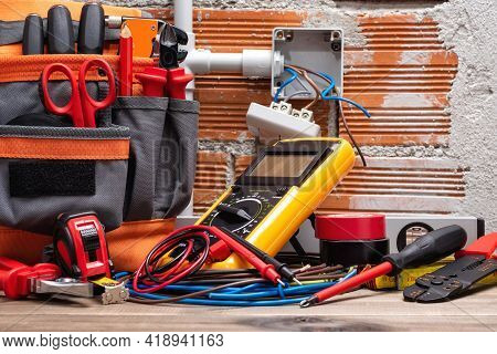 Tool Bag, Tools And Work Equipment For Electrician Technician On A Wooden Workbench. Construction In
