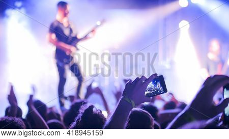 Unrecognizable Hands Silhouette Taking Photo Or Recording Video Of Live Music Concert With Smartphon