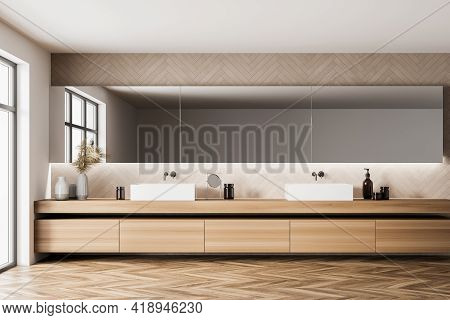 Beige Bathroom Interior With Two White Sinks And Long Mirror, Shelf With Decoration And Gels. Modern