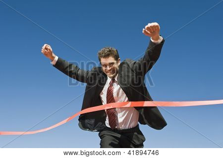 Motion blur shot of a cheerful businessman crossing the finish line of racing track against blue sky