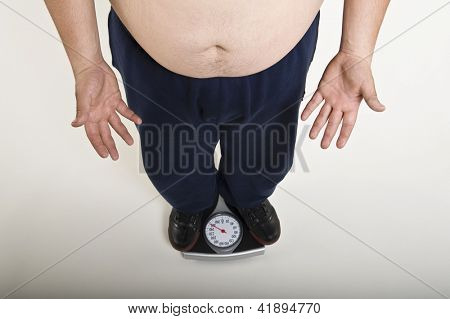 Low section of a young man measuring his weight on weighing machine