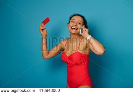 Attractive Woman With Beautiful Toothy Smile Talks On Mobile Phone And Holds A Red Blank Plastic Car