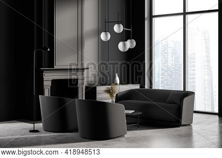 Dark Living Room Interior With Fireplace, Two Black Armchairs And Sofa, Coffee Table And Lamps On Co
