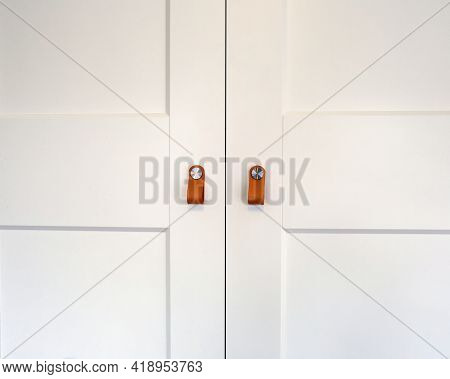 White Wooden Closet Doors With Retro Brown Leather Handles Wood Closeup Background Texture Of Cupboa