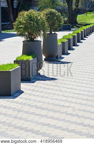 A Beautiful Alley Of Concrete Street Vases With Green Grass And Bushes Against The Backdrop Of Neatl