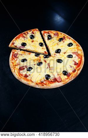 Pizza With Cheese Tomato Sauce, Olives, Fresh Mozzarella, Parmesan And Basil And Meat On A Dark Back