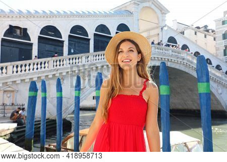 Beautiful Young Woman With A Red Dress Is Standing In Front Of The Famous Rialto Bridge In Venice, I