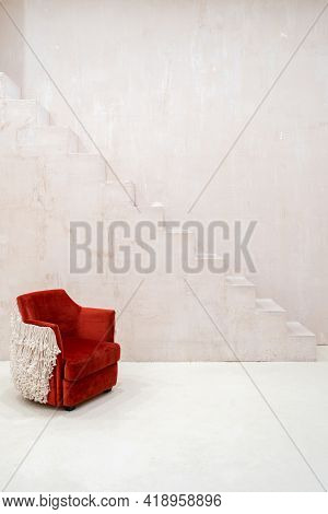 Vertical Shot Of Designers Red Velvet Armchair Against Light Concrete Textured Walls And Stairs In E