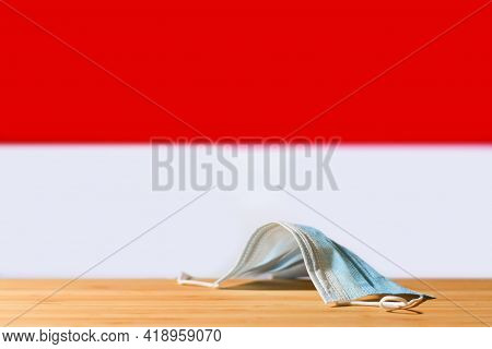 A Medical Mask Lies On The Table Against The Background Of The Flag Of Indonesia. The Concept Of A M