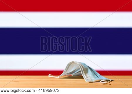 A Medical Mask Lies On The Table Against The Background Of The Flag Of Thailand. The Concept Of A Ma