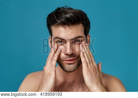 Beauty Portrait Of Handsome Man Looking At Camera With A Smile While Applying Moisturizing Cream On