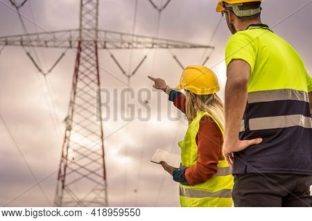 Picture Of Two Electrical Engineers Using A Tablet Standing At A High-voltage Tower To View The Plan