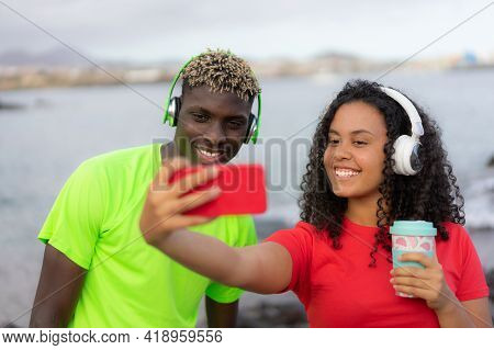 Multiracial Young Couple Traveller Happy Taking A Selfie On The Beach. Younger Influencer Making A V