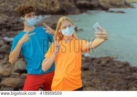 Young Couple With Protective Mask Listening Music. Boy And Girl Taking Selfie With Smart Phone,  Por
