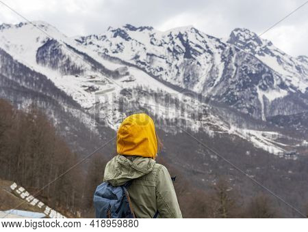 Young Woman In Yellow Hood With Backpack From Behind Enjoying The View Of The Caucasian Mountain Pea