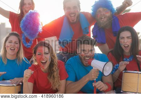 Football Fans Screaming, With Red And Blue Shirts In The Stadium. Group Of Young People Very Excited