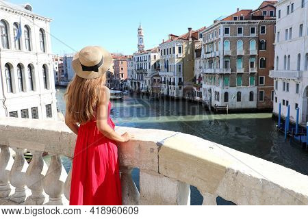 Tourism In Venice. Back View Of Beautiful Young Woman In Red Dress Enjoying View Of Grand Canal From
