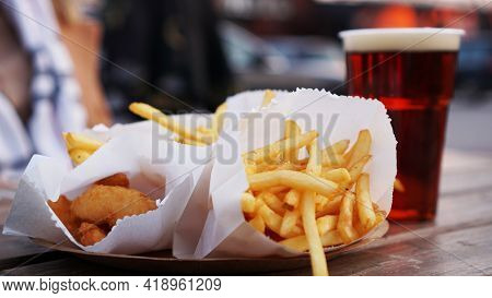 Dark Beer And Fries On A Wooden Table. Food Court. Takeaway Food, Food Festival. Unhealthy Food Conc