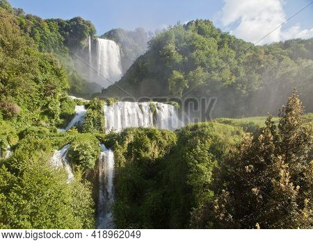 A Large Waterfall In A Forest With Cascata Delle Marmore In The Background