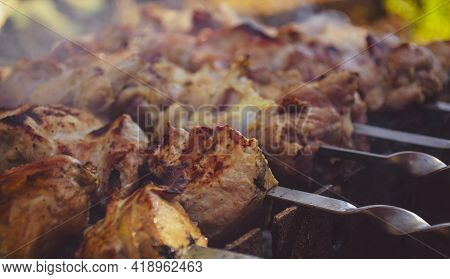 Shashlik Or Shish Kebab Preparing On Barbecue Grill Over Hot Charcoal. Grilled Pieces Of Pork Meat O