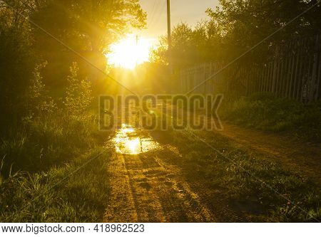 Sunset On A Rural Road In The Village After The Rain. Glare Of The Sun In The Puddles.