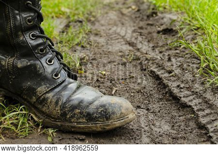 The Feet Of A Man In Boots On Muddy Country Road. Dirty Ground. Dirty Army Boots Walking On The Rain