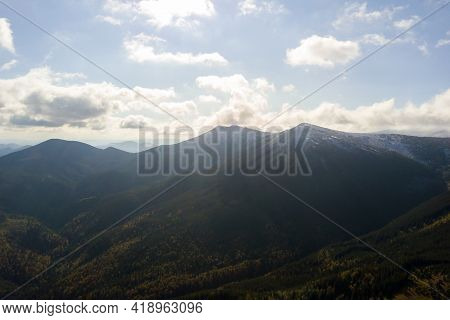 Aerial View Of Majestic Mountains Covered With Green Spruce Forest And High Snowy Peaks.
