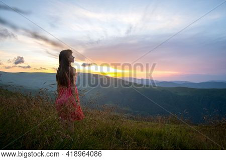 Young Woman In Red Dress Walking On Hillside Meadow On A Windy Evening In Summer Mountains.