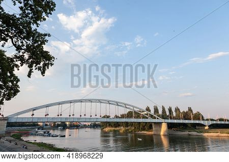 Belvarosi Hid Bridge, Also Known As Downtown Bridge On The Tisza River During A Sunny Sunset. The Br