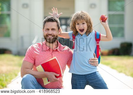 Happy Family At School Yard. Teacher In T-shirt And Cute Schoolboy With Backpack Near School Park. F
