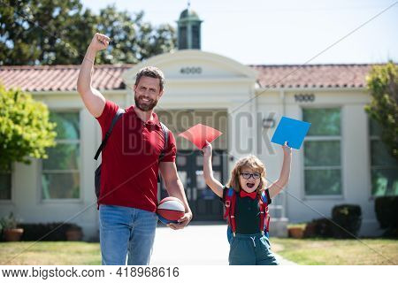 Excited Father Walking Son To School. Amazed Parent And Pupil Of Primary School Schoolboy With Backp