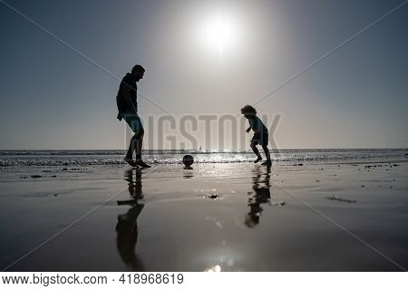 Father And Son Play Soccer Or Football On The Beach On Summer Family Holidays. Daddy With Kid Boy Pl