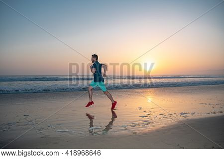 Man Running On Tropical Beach At Sunset. Full Length Of Healthy Man Running And Sprinting Outdoors.