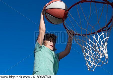 Kid Basketball Player Makes Slam Dunk. Active Child Enjoying Outdoor Game With Basketball.