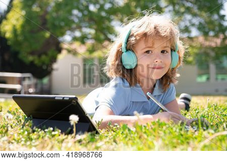 Kid Distance Learning Concept. Distance Education, Child On Online Lesson In School Park. Pupil Writ