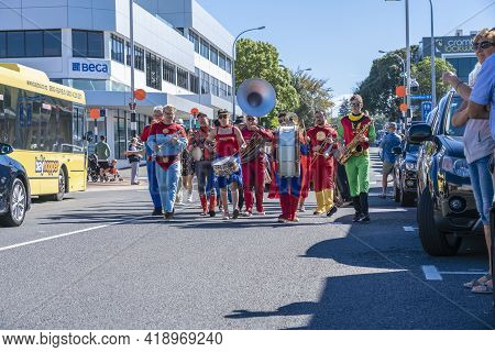 Tauranga New Zealand - April 3 2021; Superhero Band Marching Along City Street Past Buildings And Pe