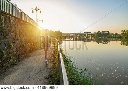 Back View Of Young Fitness Woman Running At The Waterfront With Kok River The River That Runs Throug
