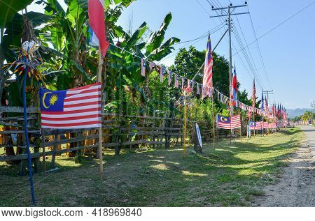 Malaysian Flags Or Jalur Gemilang Flag Bunting Hanging In A Street, A Festive Decorations In Merampo
