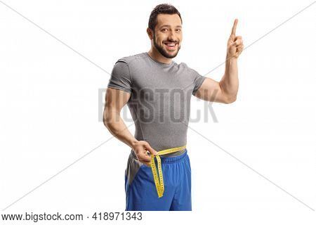Young man measuring his waist and pointing up isolated on white background